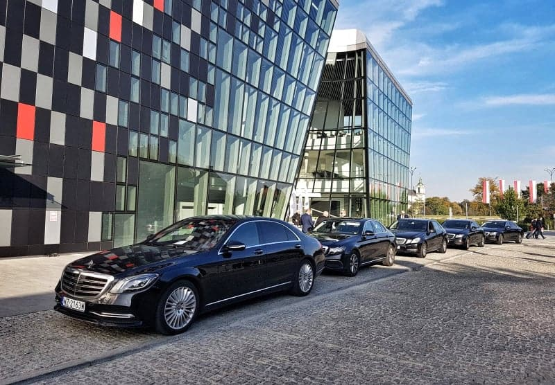 Black Mercedes-Benz cars waiting for conference participants in front of the ICE building in Krakow. Hire a car in Poland.