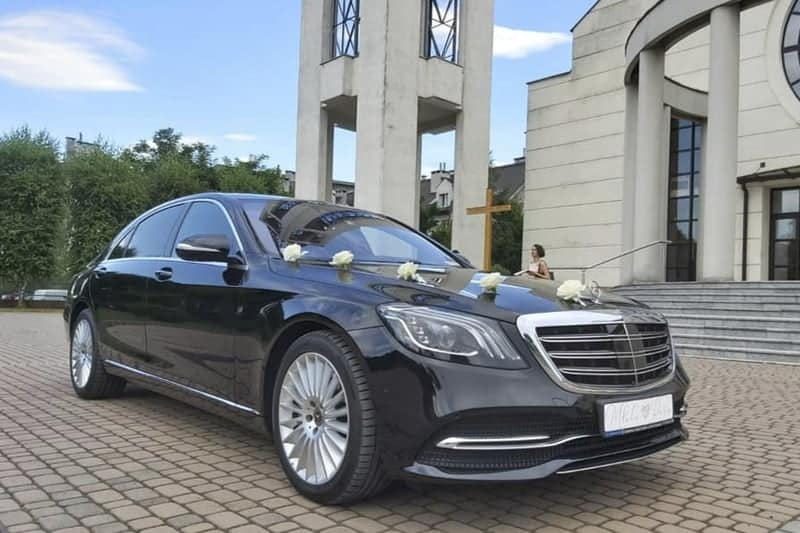 A limousine with a driver rental for a wedding decorated with a black Mercedes-Benz S-class parked in front of a church in Poland, Europe.