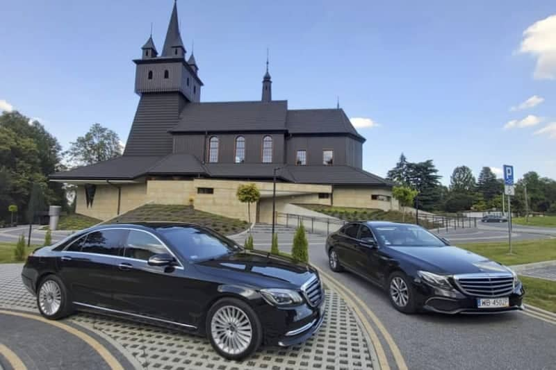 Mercedes-Benz limousine rental for a wedding and reception, S-class and E-class limousine parked in front of the church in Poland.