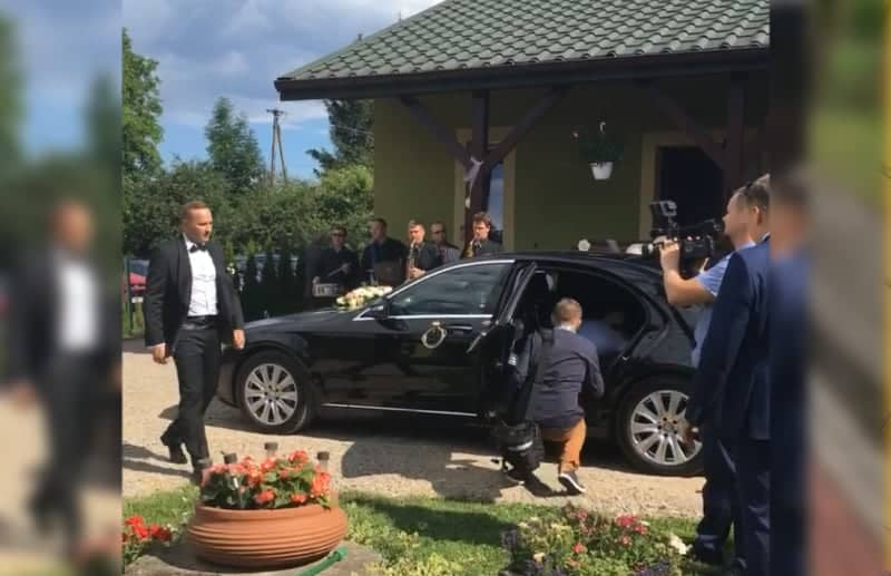 Limousine rental with a driver for a wedding in Małopolska, Poland. A driver in a suit with a decorated limousine parked in front of the bride and groom's house and surrounded by guests.